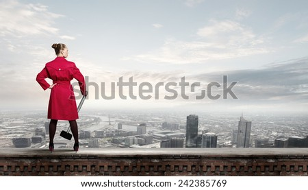 Rear view of woman in red coat with hammer in hands
