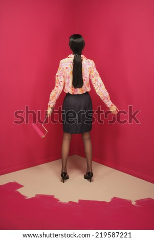 Rear view of woman painting herself into a corner - stock photo
