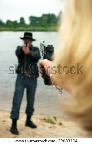 Rear view of woman pointing gun at man wearing cowboy hat, lake or river in background - stock photo
