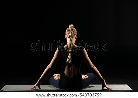Rear view of woman practicing yoga sitting in lotus position on yoga mat isolated on black