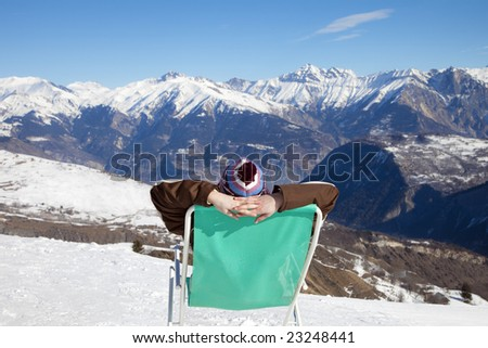 rear view of woman resting on chair in mountain - stock photo