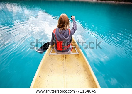 Rear view of woman rowing boat on calm water - stock photo