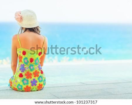 Rear view of woman sitting on the edge of swiming pool