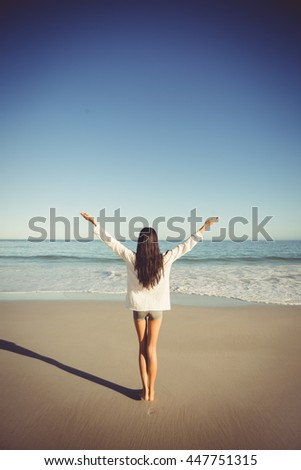 Rear view of woman standing with arms outstretched on beach