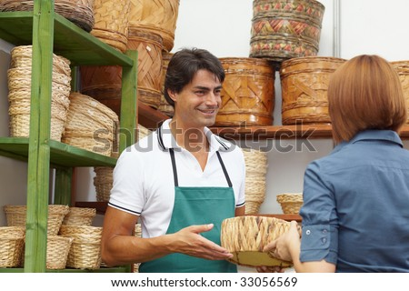 rear view of woman talking with sales clerk in flower shop - stock photo