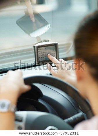 Rear view of woman typing on gps. Selective focus - stock photo