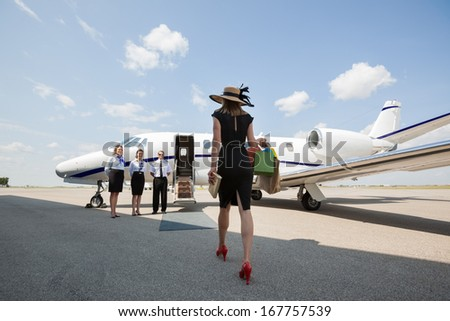 Rear view of woman walking towards private jet while pilot and stewardesses standing at airport terminal - stock photo