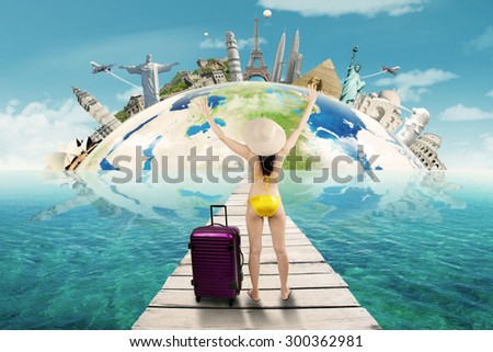Rear view of woman wearing bikini on the jetty with bag to trip on the worldwide monuments - stock photo