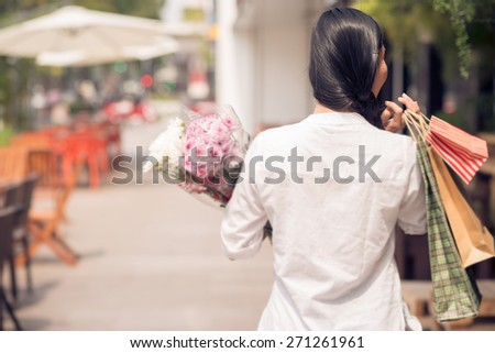 Rear view of woman with bouquets and shopping bags walking along the street, selective focus - stock photo