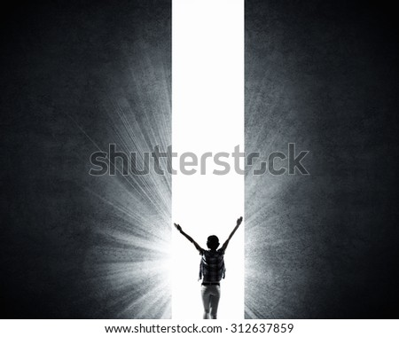 Rear view of woman with hands up entering crack in wall - stock photo