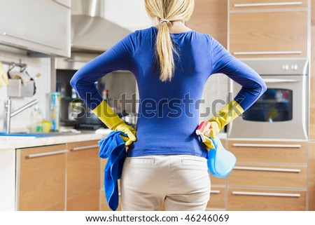 rear view of woman with yellow gloves in kitchen doing housework - stock photo