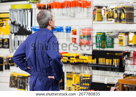 Rear view of worker with hands on hip standing in hardware store - stock photo