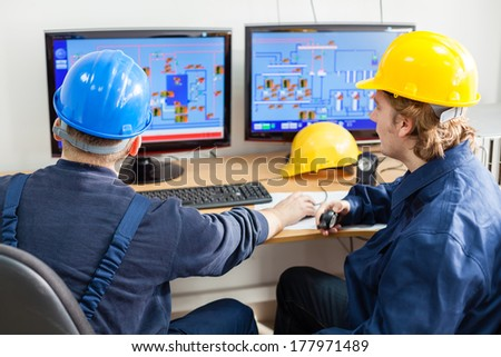 Rear view of workers in the control room, looking at computer monitor - stock photo