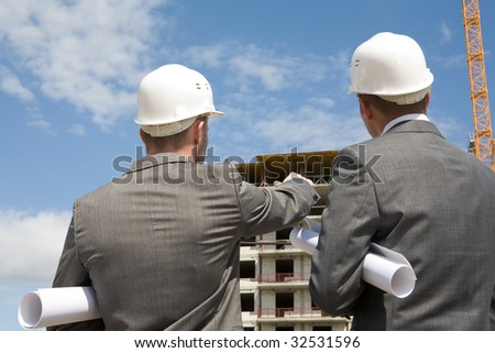 Rear view of workers interacting and looking at building