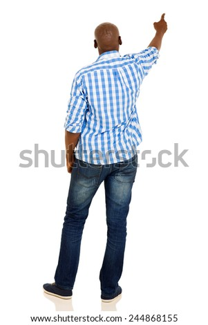 rear view of young african american man pointing at empty copy space - stock photo