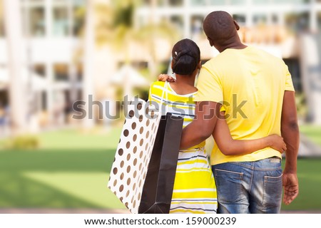 rear view of young african couple looking at modern apartment before buying - stock photo