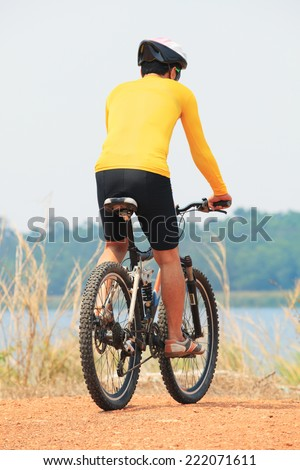 rear view of young bicycle man wearing rider suit and safety helmet riding  mountain bike on field
