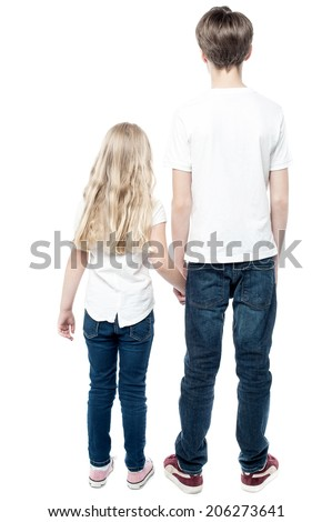 Rear view of young brother and sister with holding hands - stock photo