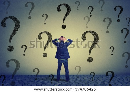 Rear view of young business man with hands on head standing in front of wall with many questions wondering what to do next. Full length of businessman facing the wall. Job work challenge concept  - stock photo