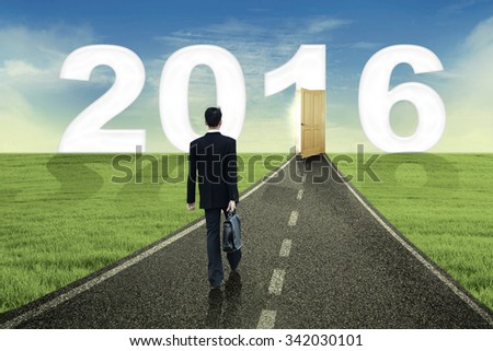 Rear view of young businessman carrying briefcase and walking on the road toward number 2016