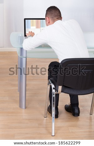 Rear view of young businessman using laptop at office desk - stock photo