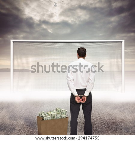 Rear view of young businessman wearing handcuffs against grey sky - stock photo