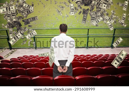 Rear view of young businessman wearing handcuffs against red bleachers looking down on football pitch - stock photo