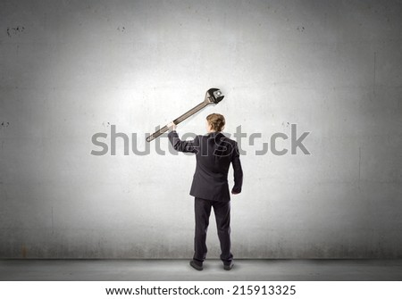Rear view of young businessman with wrench - stock photo
