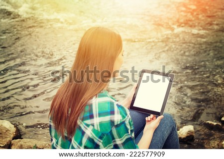 Rear view of young Caucasian brunette woman with digital tablet sitting by the river on sunny autumn day. Teenage girl in green checkered shirt and jeans with tablet computer outdoors. - stock photo