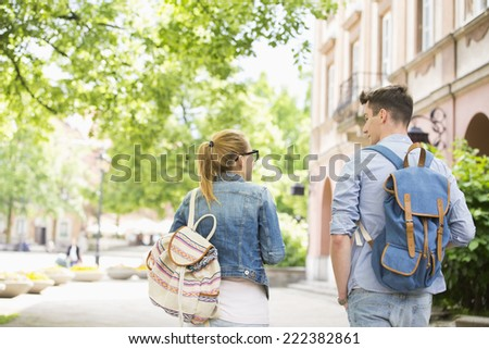 Rear view of young college friends talking while walking in campus - stock photo