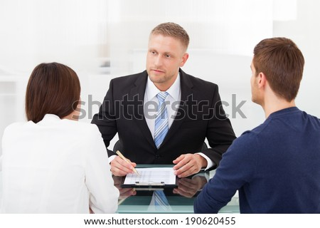 Rear view of young couple consulting financial advisor at office desk - stock photo