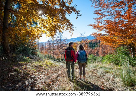 Rear view of young couple hikers holding hands and enjoying beautiful scenery on valley. Warm sunny day in the fall. Bright yellow and orange fall colors. Autumn in the mountains.