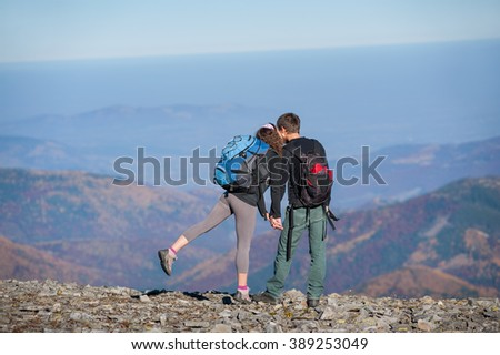 Rear view of young couple hikers with backpacks standing on the ridge of the mountain, enjoying the view of beautiful open overlook on the mountains. Couple is holding hands and kissing. Sunny day - stock photo