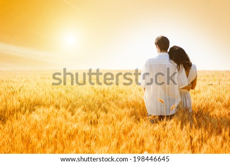 Rear view of young, couple in love in the wheat field..Sunset light, flare light, summer season, copy space - stock photo