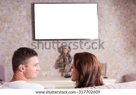 Rear View of Young Couple Looking at Each Other While Sitting on Sofa in front of Flat Screen Television Mounted on Wall of Living Room - Screen Blank for Copy - stock photo