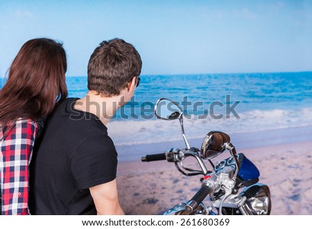 Rear View of Young Couple on Motorcycle Admiring View of Waves on Shore at Beach - stock photo