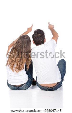 Rear view of young couple sit on ground back and point somewhere, full length portrait isolated on studio white background.