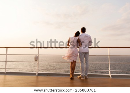rear view of young couple standing on ship deck during sunset - stock photo