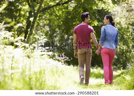 Rear View Of Young Couple Walking In Summer Countryside