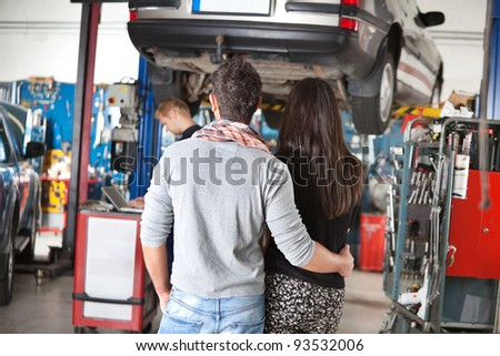 Rear view of young couple with mechanic in the background - stock photo