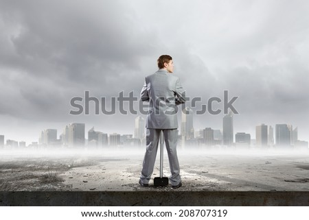 Rear view of young determined businessman with big hammer in hands