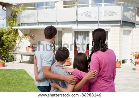Rear view of young family standing in front of their dream home - stock photo