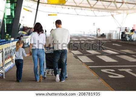 rear view of young family travelling in international airport - stock photo