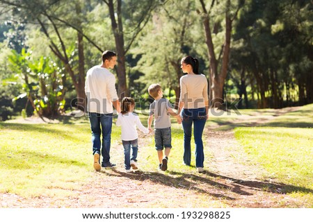 rear view of young family walking in forest  - stock photo