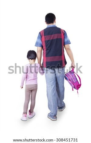 Rear view of young father walking to school with his daughter while carrying backpack, isolated on white background - stock photo