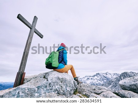Rear view of young female hiker with backpack resting on stone of cliff near wooden cross - stock photo