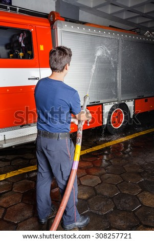 Rear view of young fireman spraying water on truck during practice at fire station - stock photo