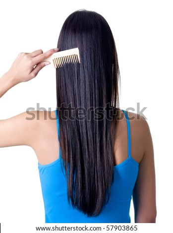 Rear view of young girl combing her healthy long hair - isolated on white