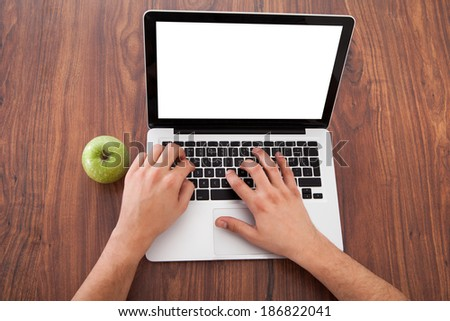 Rear view of young male college student using laptop by green apple on table - stock photo