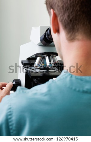 Rear view of young male researcher using microscope in hospital laboratory - stock photo